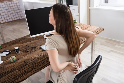 Young Businesswoman Having Back Pain Sitting On Chair At Workplace